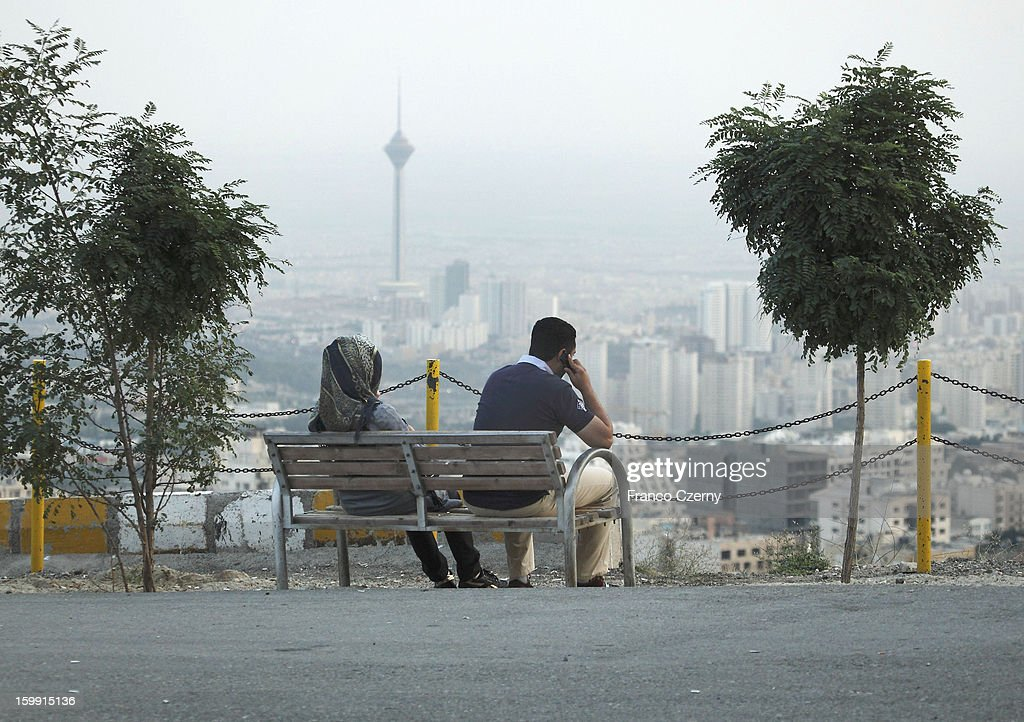 A young iranian couple relax on a bank in Tehran, Milad Tower in background on August 28, 2012 in Tehran, Iran.