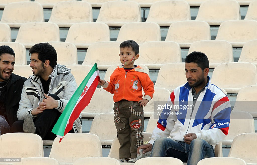 A young Iranian football fan holds the national flag during the 2015 AFC Asian Cup group B qualifying football match Iran versus Lebanon at the Azadi Stadium in Tehran on February 6, 2013. Iran won the match 5-0.