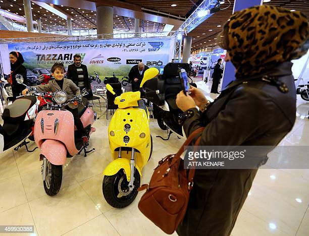 A young Iranian poses for a photo on an electronic motorcycle at an exhibition in Tehran on December 4 2014 The Iran Fuel Conservation Commission...