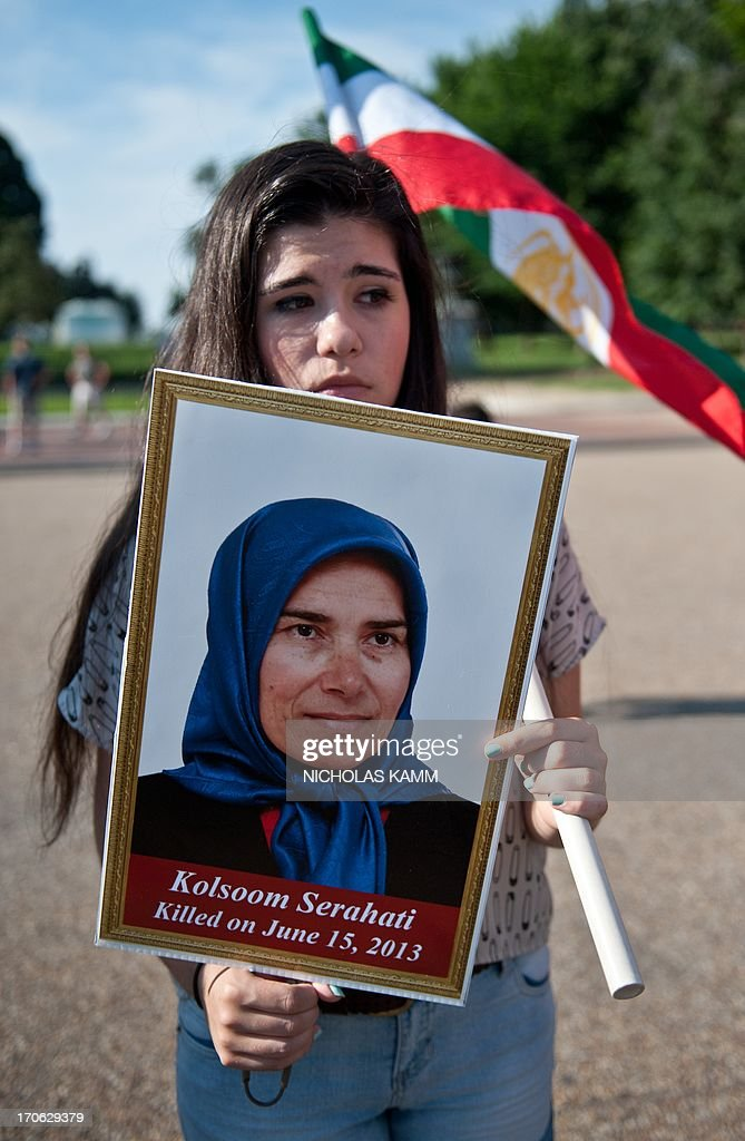 A young Iranian woman holds a photo of a woman identified as Kolsoom Serahati, one of two people said to have been killed in a deadly attack on a camp near Baghdad housing Iranian exiles, the second such assault on the group this year as its members await resettlement outside Iraq, during a demonstration in front of the White House in Washington on June 15, 2013. It was not immediately clear who was behind the attack involving at least half a dozen mortar rounds, which came as Iran tallied ballot papers from Friday's presidential election there. A police colonel, speaking on condition of anonymity, put the toll at three dead and 11 wounded from six mortar blasts, but Shahriar Kia, a spokesman for members of the People's Mujahedeen Organisation of Iran, or the Mujahedeen-e-Khalq (MEK), at Camp Liberty, said two people were killed -- one woman and one man -- and more than 30 wounded. AFP PHOTO/Nicholas KAMM