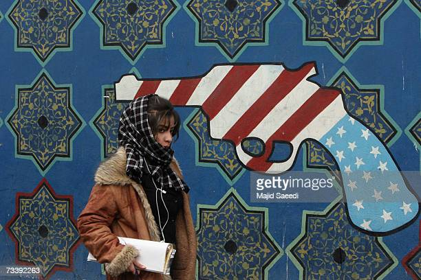 A young Iranian woman walks past a mural on the wall of the former US embassy apparently undaunted by media reports of potential airstrikes by the US...