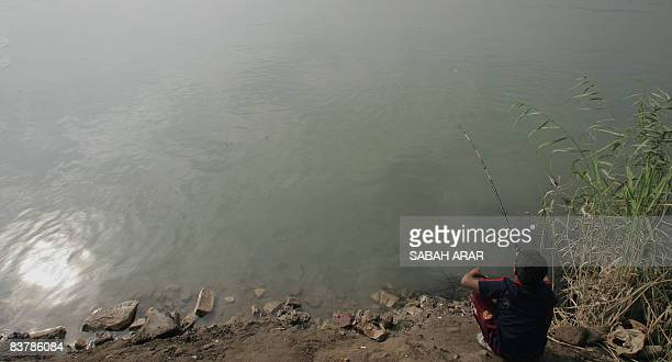 A young Iraqi boy enjoys his day off from school fishing along the banks of the Tigris River which runs through central Baghdad on November 22 2008...