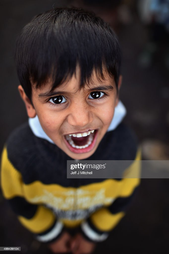 A young Iraqi boy poses for a photograph in the camp known as the 'New Jungle' on December 1, 2015 in Calais, France. Thousands of migrants continue to live in the makeshift camp in the port town in northern France, where they continue to try and board vehicles heading for ferries or through the tunnel in an attempt to reach Britain.