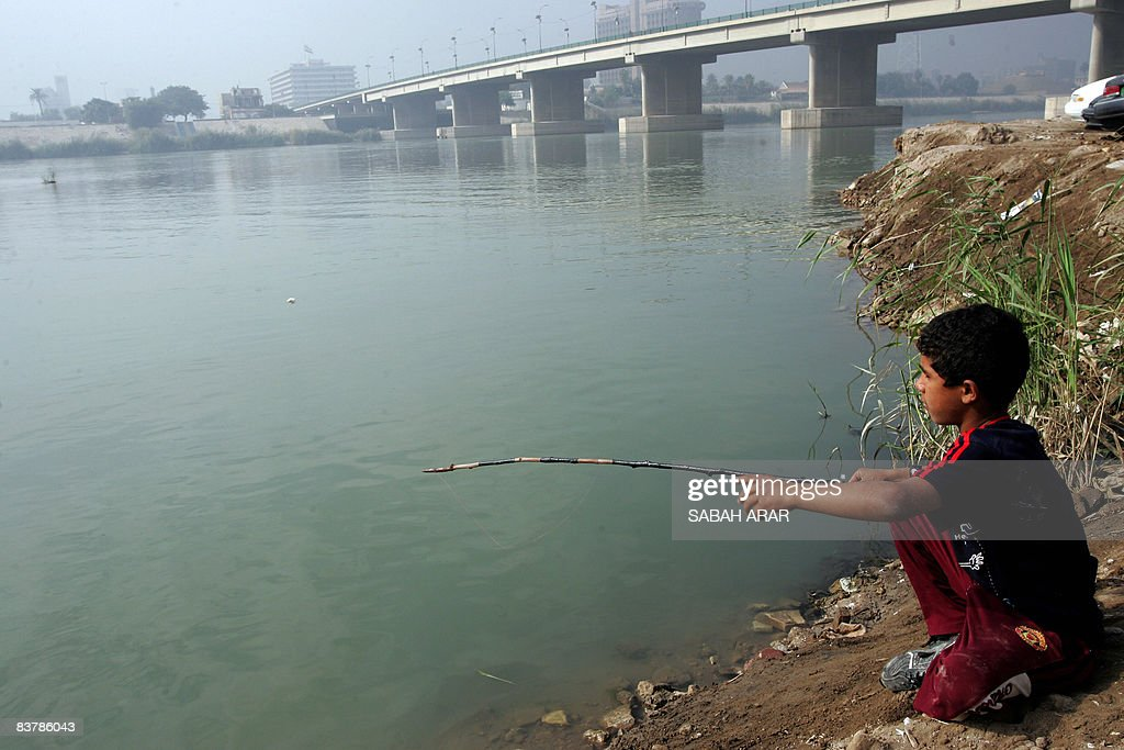 A young Iraqi boy throws his line in as he enjoys his day off from school fishing along the banks of the Tigris River which runs through central...