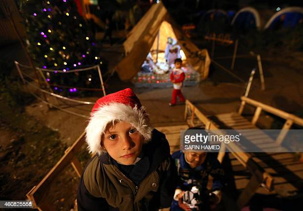 A young Iraqi Christian poses in front of a Nativity scene displayed in a tent erected in the grounds of the Mar Elia Chaldean Catholic Church where...