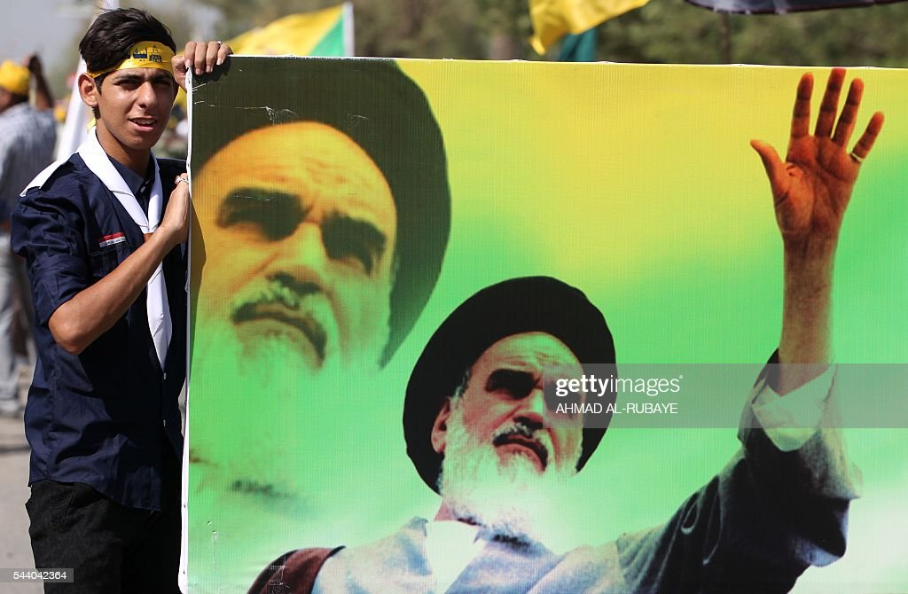 An Iraqi young man holds a banner bearing a portrait of late revolutionary leader Ayatollah Ruhollah Khomeini during a parade marking al-Quds (Jerusalem) Day in the capital Baghdad, on July 1, 2016. / AFP / AHMAD