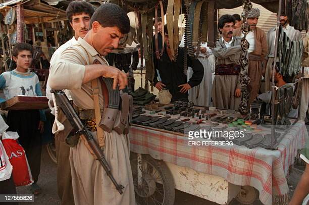 A young Iraqi peshmerga loyal to the Kurdistan Democratic Party of Massud Barzani buys a Kalashnikov magazine at the Erbil weapons market 19...