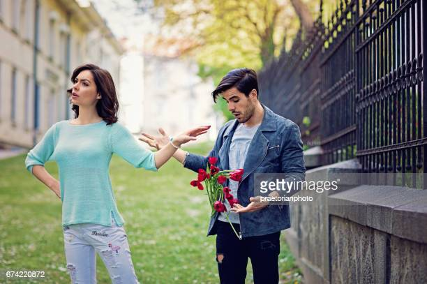 Young is girl is rejecting boy throwing his flowers