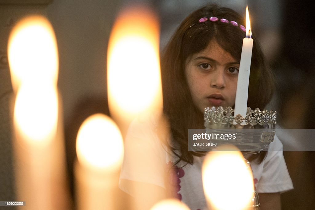 A young Israeli Arab Christian holds candles during an Easter mass led by Parish priest, Father Suheil Khoury (unseen) on April 21, 2014 in the church of the Palestinian village of Iqrit, sprawled on a hilltop in the Upper Galilee. The church is the only remaining structure following the evacuation of the residents in 1948. Sixty-six years after their ancestors were driven out during the Nakba, the 'catastrophe' that befell Palestinians, Arab Israeli youths are returning to the village of Iqrit in the Upper Galilee.