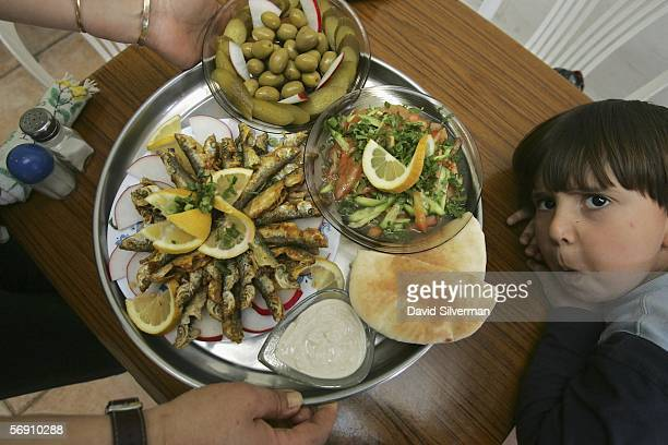 Young Israeli boy Yossi Ben Shabat looks up as his mother Jeanette carries a meal of fried sardines with tehina sauce fresh pita a cucumber and...