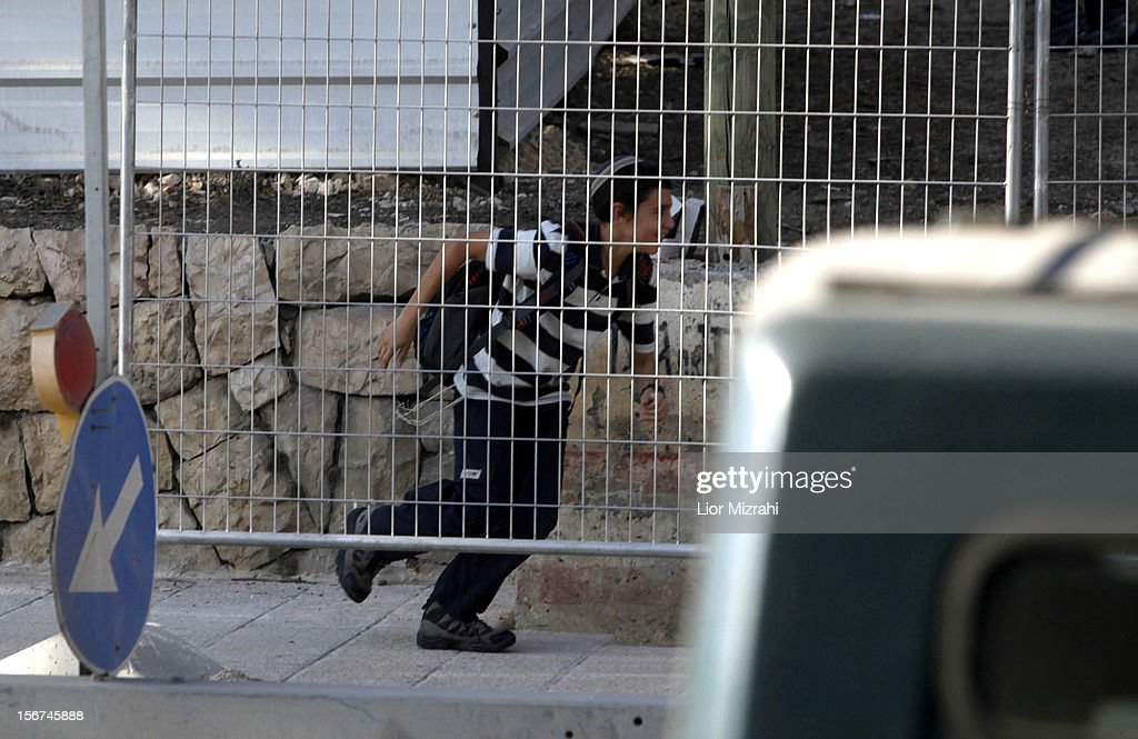 A young Israeli man takes shelter as an air raid siren sounds on November 20, 2012 in Jerusalem, Israel. Hamas militants and Israel are continuing talks aimed at a ceasefire as the death toll in Gaza reaches over 100 with three Israelis also having been killed by rockets fired by Palestinian militants.