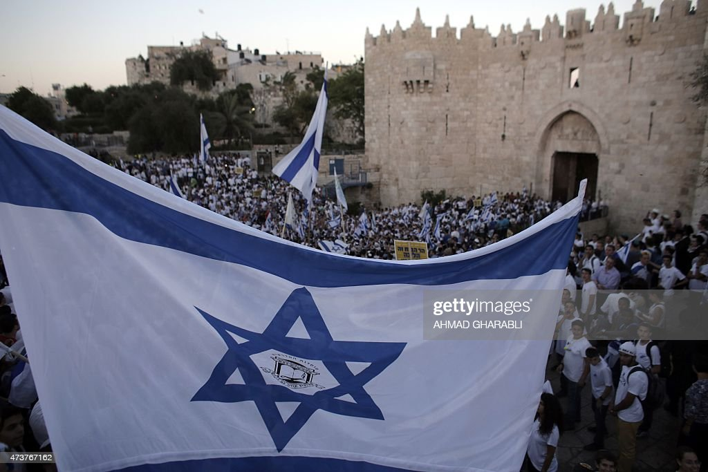 Young Israeli nationalists wave national flags outside Damascus Gate in Jerusalem's old city on May 17 as they take part in the 'flag march' to mark...