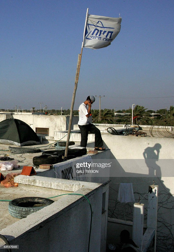 OUT A young Israeli settler stands on the roof of the Palm Beach Hotel where dozens of rightwing Israelis have set up base in a bid to thwart the...