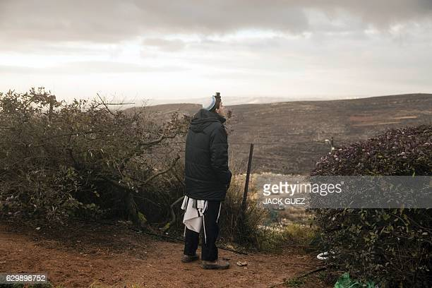 TOPSHOT A young Israeli settler wearing Jewish prayer artefacts watches the landscape in the settlement outpost of Amona which was established in...
