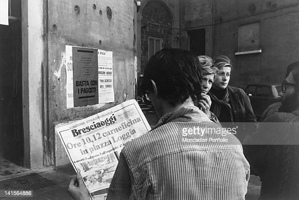 A young Italian man reading the extra edition of the newspaper 'Bresciaoggi' after the Piazza della Loggia bombing Brescia 28th May 1974
