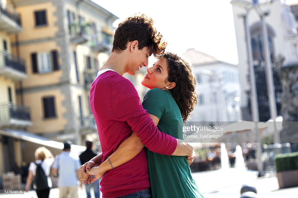 Young Italians greeting each other on City street : Stock Photo