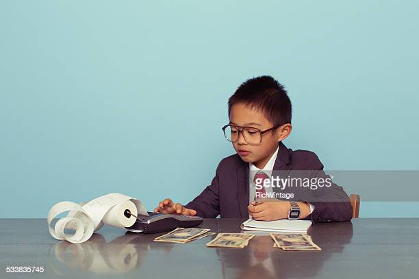 Young Japanese Boy Accountant in Business Suit Adds Numbers