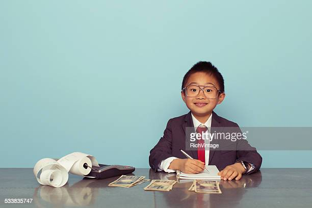 Young Japanese Boy in Business Suit plays Accountant