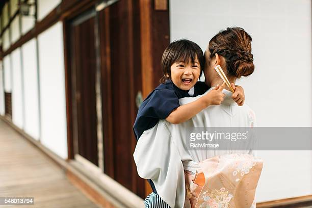 Young Japanese Boy is Laughing in Mother's Arms