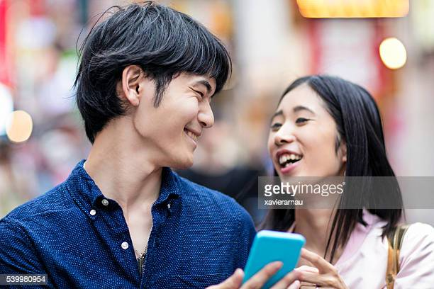 Young Japanese couple laughing watching a mobile phone message