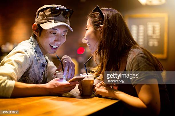 Young Japanese couple using mobile phone in a cafe