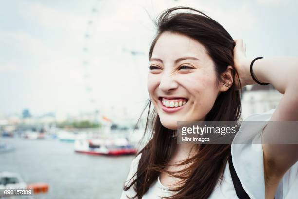Young Japanese enjoying a day out in London, standing by the River Thames, London Eye in the background.