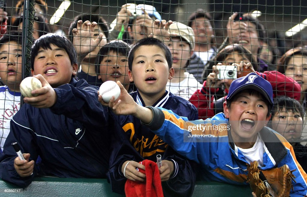 Young Japanese fans shout to players for autographs before the start of a preseason friendly game between Boston Red Sox and Yomiuri Giants at Tokyo...