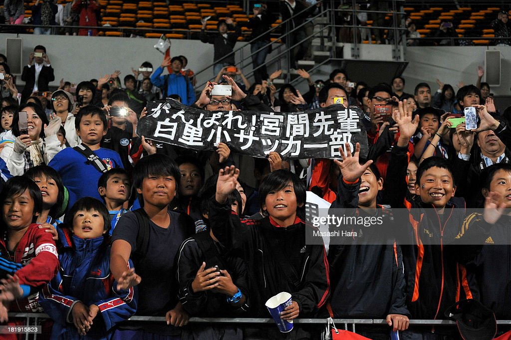 Young Japanese fans wave after the Women's international friendly match between Japan and Nigeria at Fukuda Denshi Arena on September 26, 2013 in Chiba, Japan.
