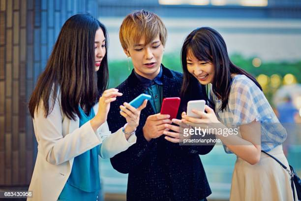 Young japanese friends are looking in their mobile phones
