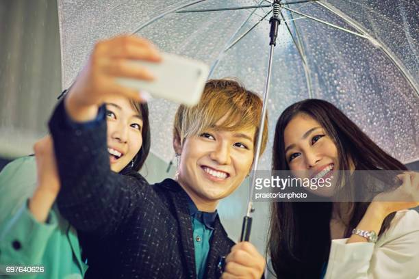 Young japanese friends are taking selfie in the rainy night
