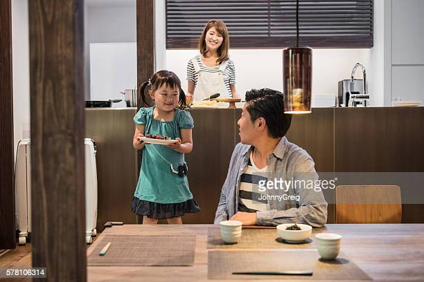 Young Japanese girl carrying food to father at table