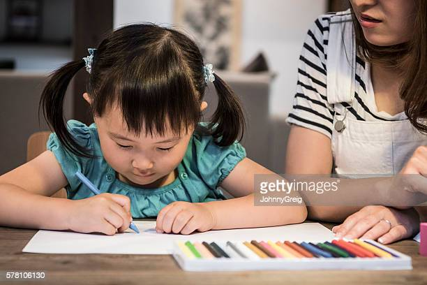 Young Japanese girl drawing at home with her mother