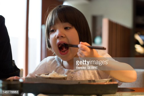 young japanese girl eating sashimi foto stock getty images