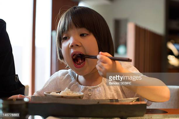 Young Japanese girl eating sashimi