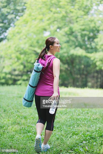 Young Japanese girl with water bottle after training in the park