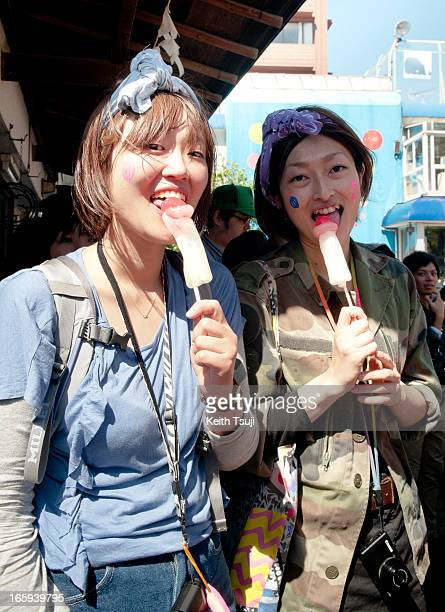 Young Japanese girls eat phallicshaped candy lollipops at Kanamara Matsuri on April 7 2013 in Kawasaki Japan The festival is held annually on the...
