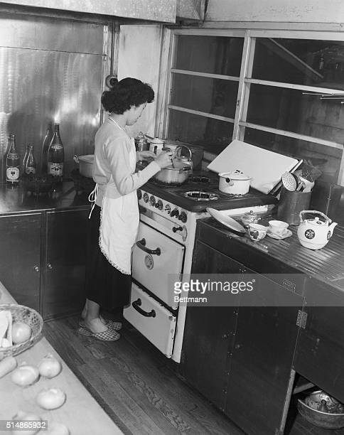 A young Japanese housewife cooks using a new gas range in the kitchen of her Tokyo home