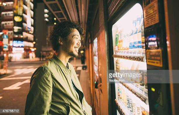 Young japanese man buys drink from the machine