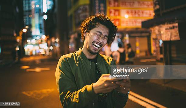 Young japanese man texting on the phone