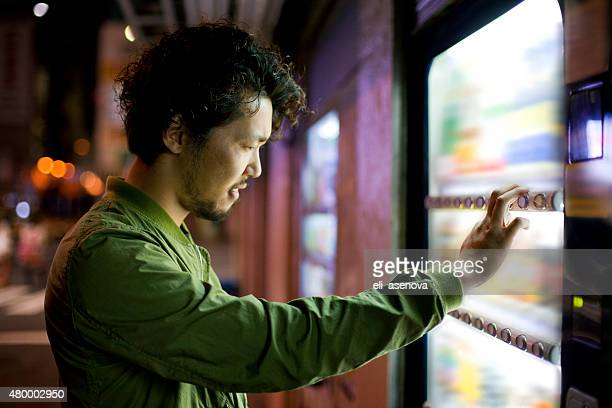 Young Japanese Man Using Vending Mashine in Tokyo.
