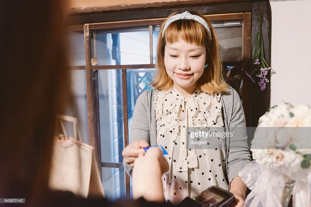 Young Japanese Shop Owner Smiles as Customer Pays for Purchases