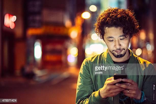 若い日本のティーン、電話で屋外での都会の風景
