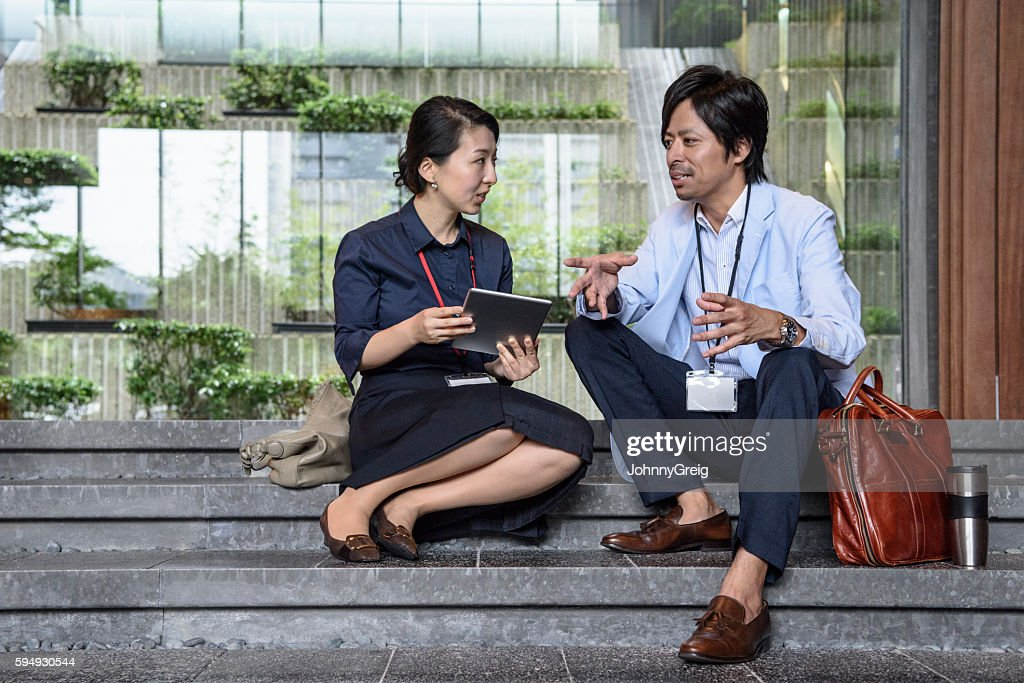 Young Japanese woman and man sitting on steps talking
