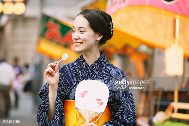 Young Japanese woman in a traditional kimono at a summer festival