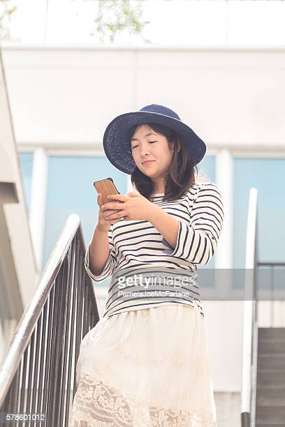 Young Japanese Woman Playing Augmented Reality Game on Mobile Phone