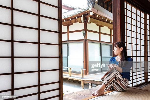 Young Japanese woman relaxing in a peaceful Buddhist temple