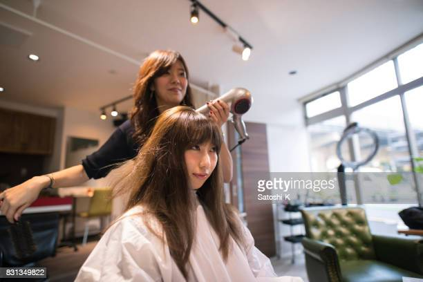 Young Japanese woman setting up hair in beauty salon