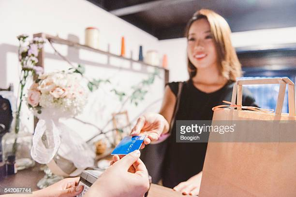 Young Japanese Woman Shopping Smiles as She Pays for Purchases