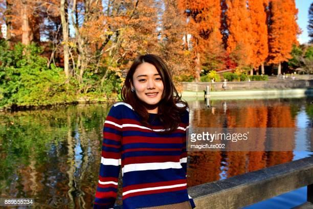 東京井の頭公園の美しい秋の紅葉に対する橋の上に立って日本の若い女性