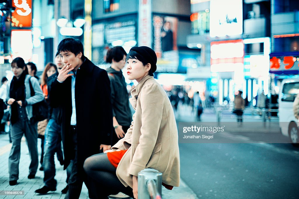 A young Japanese woman waiting for her friends, sitting on a railing along a busy, crowded sidewalk in Shibuya in the evening.
